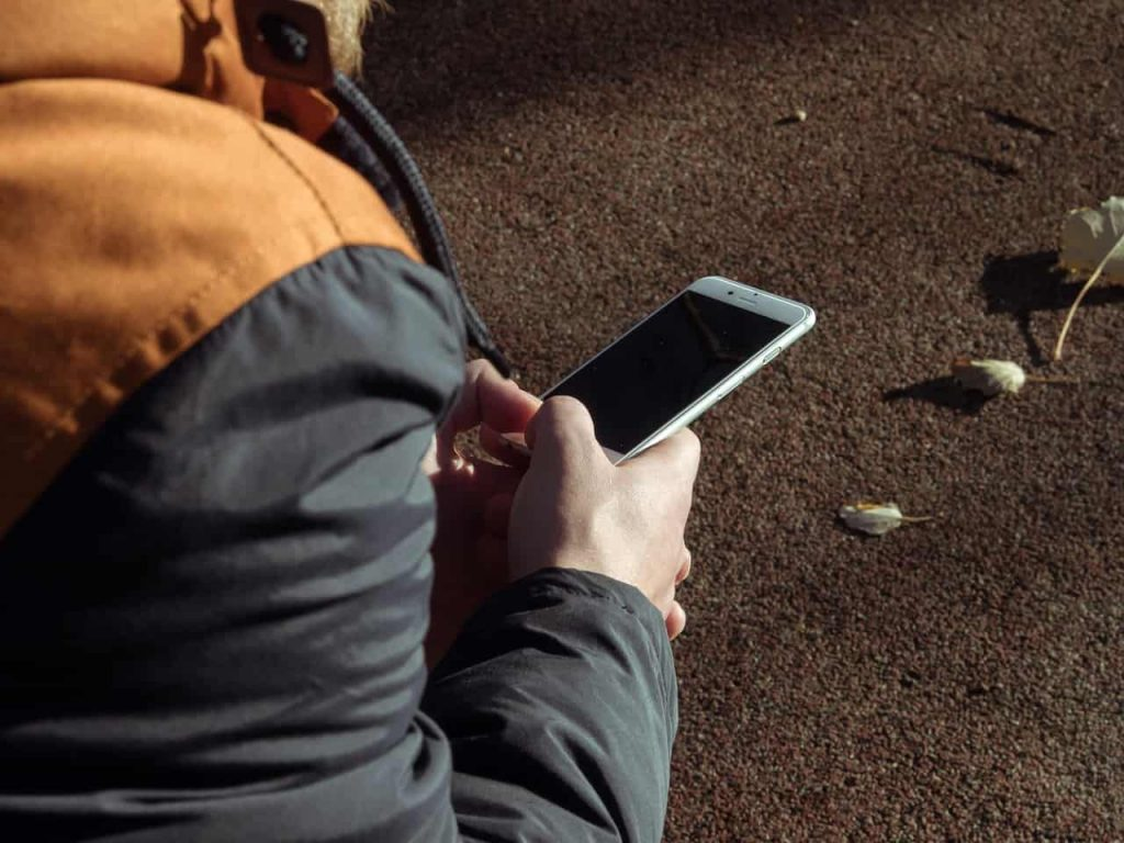 Side View Of Boy Playing With Iphone